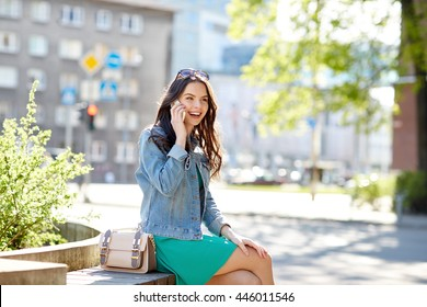 technology, communication, lifestyle and people concept - smiling young woman or teenage girl calling on smartphone on city street