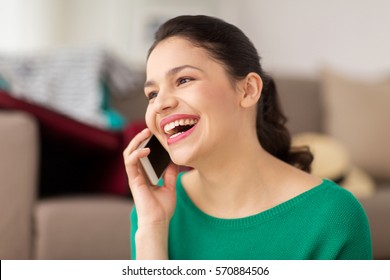 technology, communication and people concept - happy young woman calling on smartphone and laughing at home