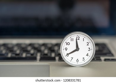 Technology, compter and Time  concept. Close up of vintage round clock on laptop notebook.