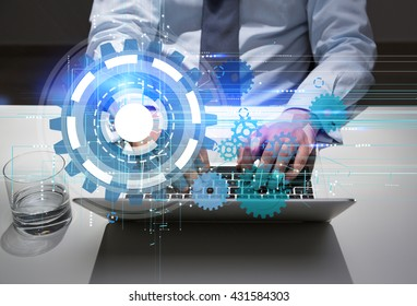 Technology concept with businessman using laptop with abstract digital cogwheel pattern on desktop with glass of water