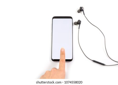 Technology concept, hand holding or torch smartphone and using a new modern smartphone with white screen and black headphone cable, isolated on white background with clipping path top view.