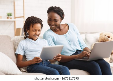 Technology Concept. Happy black family sitting on sofa, using laptop and digital tablet at home, free space
