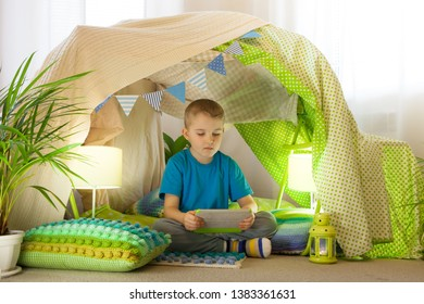 technology concept - happy boy with tablet pc computer in kids tent at home
