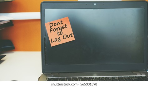 A Technology concept image of a laptop with black screen on an office desk with a red sticky note contain word Dont Forget To Log Out