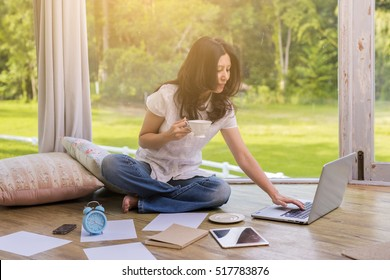 Technology, education, business concept - Smiling asian woman drinking coffee with laptop computer at home and background blur beautiful garden at home. (vintage color tone, lens blur effect)