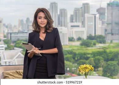 Technology, education, business concept - Smiling asian woman hold tablet computer, looking to camera and building skyscrapers in the background. (lens blur effect)