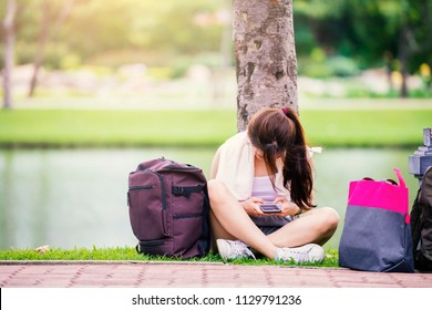 Technology, Education, Remote working Concept - Sad young asian woman is reading text message on mobile phone while sitting in the park and searching information on cell telephone. copy space
