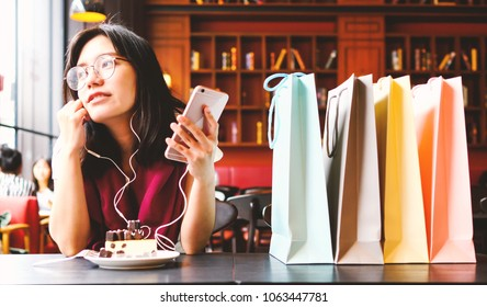 Technology, Entertainment Concept - Relaxing after shopping. Beautiful asian woman with mobile phone listening to music, eats delicious cake and shopping bags in coffee shop.