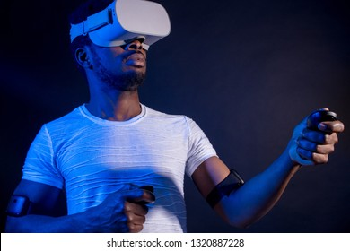 Technology, entertainment, gaming, cyberspace and people concept. Serious dark-skinned player wearing white t-shirt and white modern 3-D glasses. Black man playing video game with VR headset