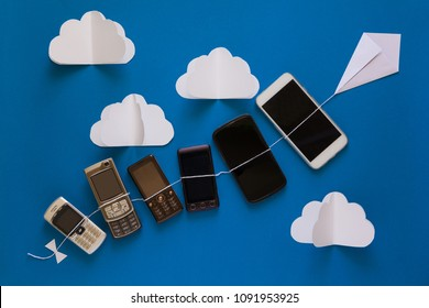Technology evolution concept. Vintage and new phones flying on paper kite on blue sky. Origami. Paper cut. Top view
