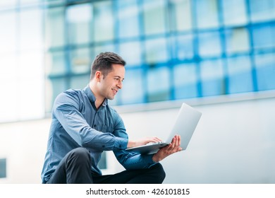 Technology expert using a laptop outdoors in an urban area.