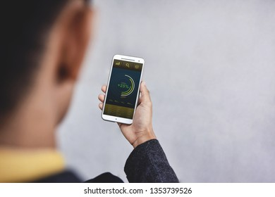 Technology in Finance and Business Marketing Concept. Graphs and Charts show on Smartphone's Screen. Modern Businessman seeing Statistical Data on Mobile Phone. Over the Shoulder View