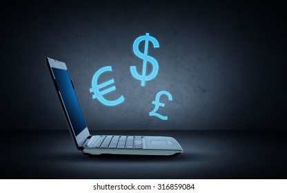 technology, finances and exchange rate concept - open laptop computer with blue lighting currency symbols over dark gray background
