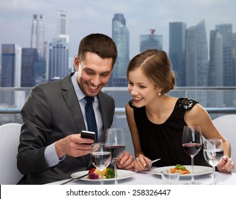 technology, food, holidays and people concept - smiling couple with smartphone eating at restaurant over city background