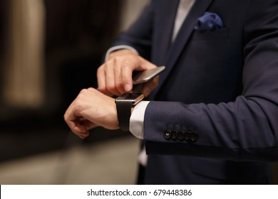 Technology, gadget and consumerism. Close-up of businessman using smart watch application and mobile phone