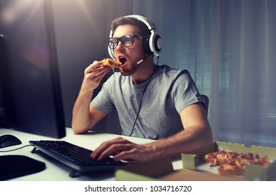 technology, gaming, entertainment, let's play and people concept - young man in headset with pc computer eating pizza while playing game at home and streaming playthrough or walkthrough video