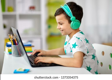 technology, gaming and people concept - boy in headphones playing video game on laptop computer at home