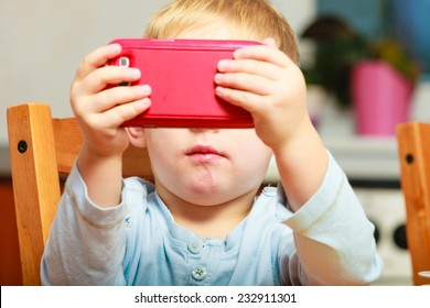 Technology generation. Happy childhood. Little boy child dirty mouth drooling, eating breakfast playing with mobile phone at table. Home.