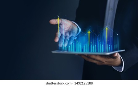 Technology, High Profit, Stock Market, Business Growth, Strategy Planing concept. Businessman in Suit Present Graphs and Charts information on digital tablet