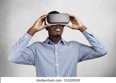 Technology, innovation and cyberspace concept. Amazed African employee in blue shirt having fun and entertaining himself while playing video games in office during break, using oculus rift headset