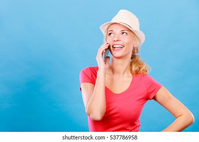 Technology, international talks, modern devices concept. Tourist woman in sun hat talking with someone through smartphone. Studio shot on blue background