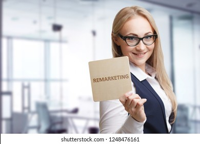 Technology, internet, business and marketing. Young business woman writing word: Remarketing