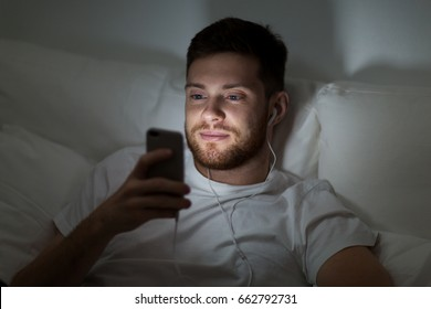 technology, internet, communication and people concept - happy smiling young man with smartphone and earphones listening to music in bed at night