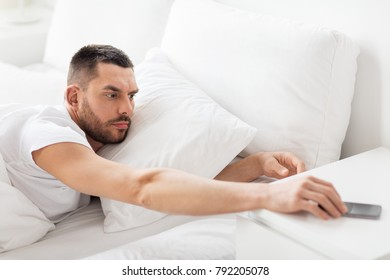 technology, internet, communication and people concept - young man reaching for smartphone in bed at home in morning