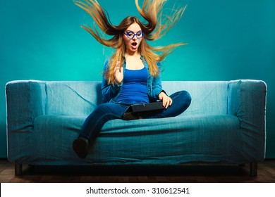 Technology internet concept. Fashion woman wearing denim sitting with tablet on couch hair blowing face expression blue color