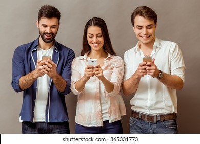 Technology and internet concept: group of young people looking at their smartphones, on a gray background