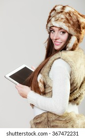 Technology internet concept. Happy fashion woman in winter clothes fur cap using digital tablet computer studio shot on gray