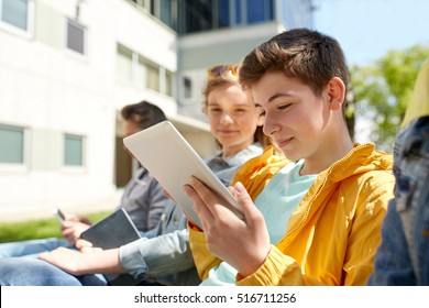 technology, internet and people concept - group of happy teenage friends or high school students with tablet pc computer outdoors