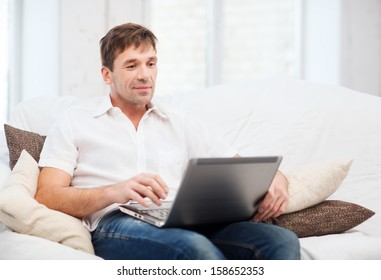 technology and lifestyle concept - man working with laptop at home