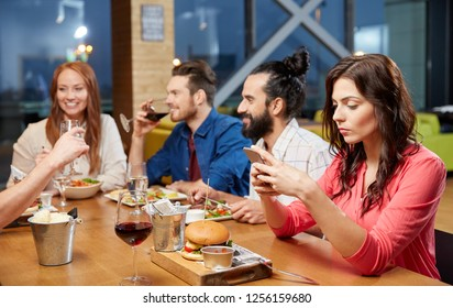technology, lifestyle and people concept - bored woman dining with friends and messaging on smartphone at restaurant