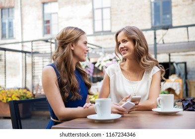 technology, lifestyle and people concept - happy young women with smartphones drinking coffee at cafe outdoors