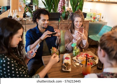 technology, lifestyle and people concept - happy friends with smartphones taking picture of food at restaurant