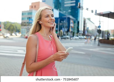 technology, lifestyle and people concept - smiling young woman with smartphone and earphones listening to music in city