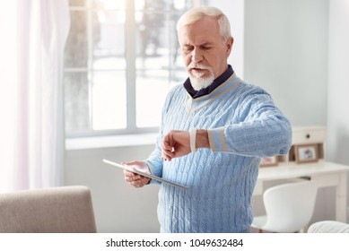 Technology lover. Charming elderly man holding a tablet and checking his smart watch while standing in the middle of the living room