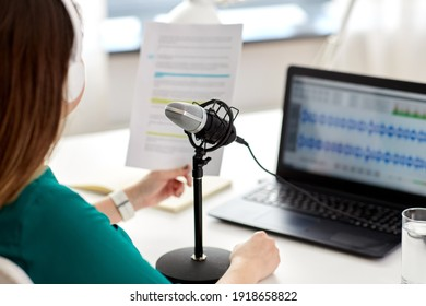 technology, mass media and people concept - close up of woman with microphone and laptop computer talking and recording podcast at studio