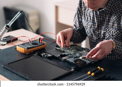 technology microelectronics science education. engineer student inspecting disassembled broken laptop and removing motherboard
