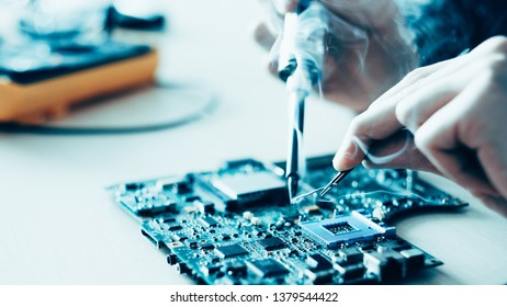 Technology microelectronics science education. Engineer student learning to solder electronic component on computer motherboard.