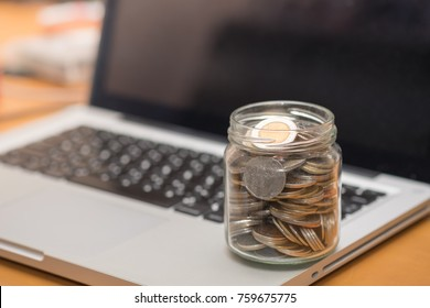 Technology, money and saving concept. Clear bottle with full of coins on laptop computer.