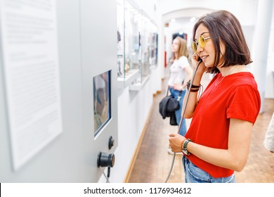 Technology museum, BERLIN, GERMANY - 19 MAY 2018: Asian Woman looking at museum exhibition, and listening audio guide using headphones in modern gallery. Education and leisure concept