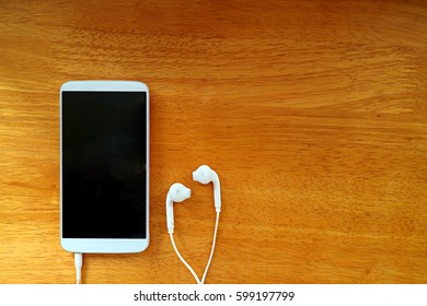 technology, music, gadget and object concept - close up of white smartphone and earphones on wooden surface