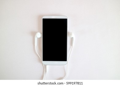 technology, music, gadget and object concept - close up of white smartphone and earphones