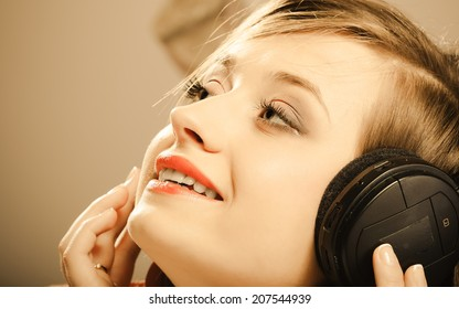 Technology, music and happiness concept - smiling girl teenage in headphones listening music. Sepia color, vintage photo
