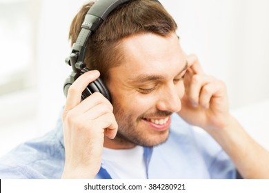 technology, music and people concept - smiling young man in headphones at home