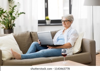 technology, old age and people concept - happy senior woman in glasses with laptop computer and glass of wine at home