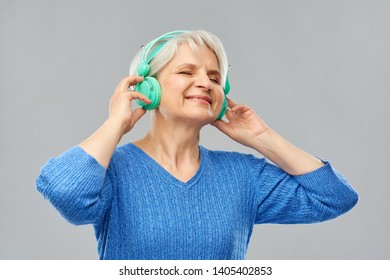 technology and old people concept - smiling senior woman in glasses and headphones listening to music over grey background