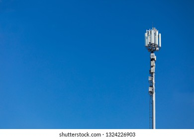 Technology on the top of the telecommunication GSM. Masts for mobile phone signal. Tower with antennas of cellular communication on the background of blue sky. Copy space on left side.